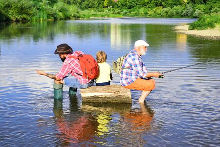 Generations men. Family fishermen fishing with spinning reel. Grandfather, father and son are fly fishing on river