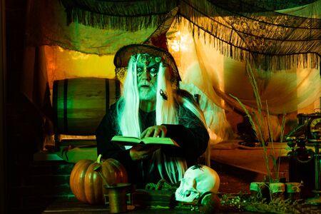Bearded man dressed like Halloween monster. Bloody skin for Halloween. The crazy joker face. Devil vampire man