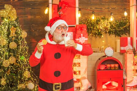 Portrait of Santa Claus Drinking milk from glass and holding cookies. Christmas Beard style. Merry Christmas. Santa Claus in Santa hat. Christmas food and drink 版權商用圖片