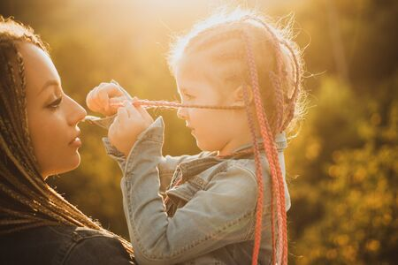 Hair in trendy weave plait. Happy loving family - mother and daughter. Braiding hair. Nice child girl with plaits
