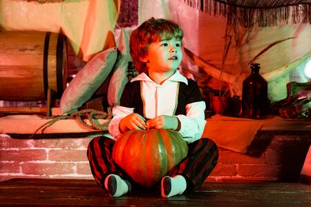 Funny kid in carnival costumes indoors. Children in America celebrate Halloween. Halloween decorations. Cheerful child with pumpkins and candy.