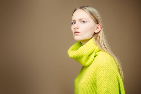 Close-up attractive european blonde woman long hair, tilting head, standing in a half-turn, wearing casual green outfit. Suspicious view and listening notation. Stok Fotoğraf
