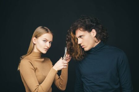 Girl scheming an evil plan of cutting off a curly hair in a man. A smart wily woman has wonderful schemes like a crook of a friend, a dark background. The concept of family betrayal. Revenge of a man for bad intent by cutting his hair. Stock Photo