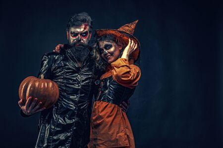 Familia feliz celebrando para Halloween. Jack-o-lanterns. Feliz pareja gótica en traje de Halloween. Truco o trato.