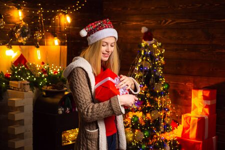 Christmas and happiness concept - a beautiful woman in Santa hat helper with Christmas gift in a red box. Rituals for the New Year.