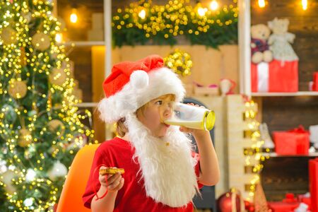 Santa fun. Merry Christmas and happy new year. Santa holding cookie and glass of milk on Christmas tree background. Santa in home