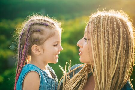 Mother and child girl playing and hugging. Braiding hair. Nice child girl with plaits. Hair in trendy weave plait. Stock Photo