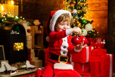 Gifts for winter holidays at fire place. Little boy with Christmas presents. Joy and happiness. Childhood moments. Child cheerful face got gift at christmas. Check contents of christmas stocking.