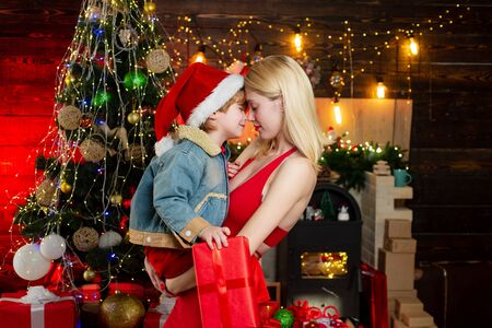 Mother and baby son celebrate christmas at home. Winter holidays concept. Magic atmosphere family holidays. Parenthood joy. Motherhood child care. Spend holiday time with closest. Family love Stock Photo