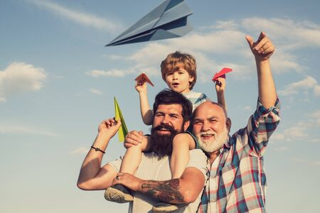 Men generation. Young boy with father and grandfather enjoying together in park on blue sky background. Three men generation. Happy men loving family. Dad and son. Stock Photo - 132077030