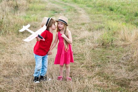 Kids kiss. Love story for cute children. Romantic and love. Childhood on countryside. Beautiful little couple - boy and girl embracing.