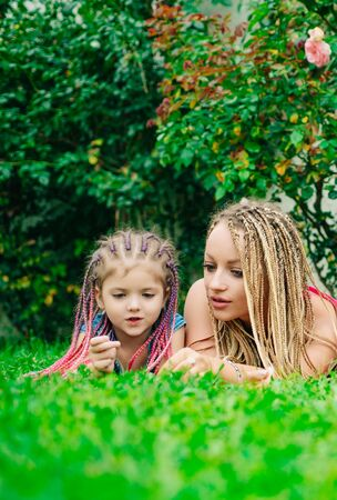 Lifestyle portrait mom and daughter in happy mood on grass. Happy mother hugging her daughter. Braiding hair. Stock Photo