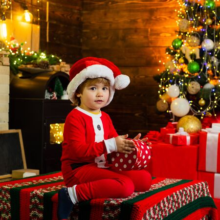 Childhood memories. Boy cute child cheerful mood play near christmas tree. Family holiday. Merry and bright christmas. Lovely baby enjoy christmas. Santa boy little child celebrate christmas at home