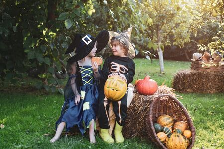 Children sister and brother with pumpkin dressed like skeleton and witch for Halloween party. Halloween portrait of happy cute child.