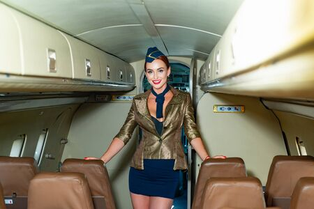Beautiful charming stewardess dressed in official blue uniform staying inside the plane in airport. Travel concept. Stewardess dressed in uniform in the passenger cabin of the aircraft.