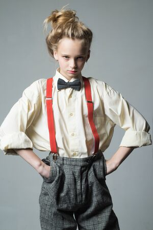 Cool and confident. retro fashion model. vintage charleston party. teen girl in retro male suit. suspender and bow tie. old fashioned child. vintage english style. jazz step fashion