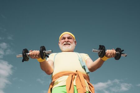 Senior man in gym working out with weights. Senior man lifting dumbbell. Be in motion. Summer and active holidays. Grandfather sportsman portrait on blue sky backgrounds.