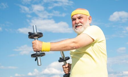 Freedom retirement concept. Grandfather exercising with dumbbell. Sport for senior man. Stock Photo