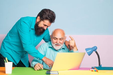 Two male senior man employees consulting with laptop in office. Conversation between colleagues in office. Business people having meeting around table in modern color office.