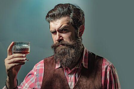 Hipster con barba y bigote en traje bebe alcohol después de la jornada laboral. Hombre o empresario bebe whisky sobre fondo negro.