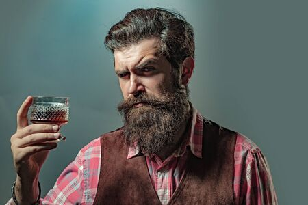 Hipster with beard and mustache in suit drinks alcohol after working day. Man or businessman drinks whiskey on black background. Фото со стока
