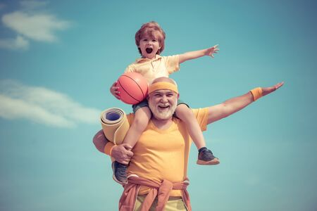 Sportsman grandfather and healthy kid with basketball ball on blue sky background. Sport for little children. Different generations.