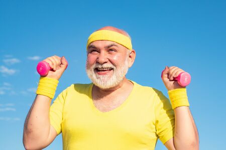 Senior male is enjoying sporty lifestyle. Happy Senior man exercising with lifting dumbbell outdoor. Elderly man after her workout. Stock Photo