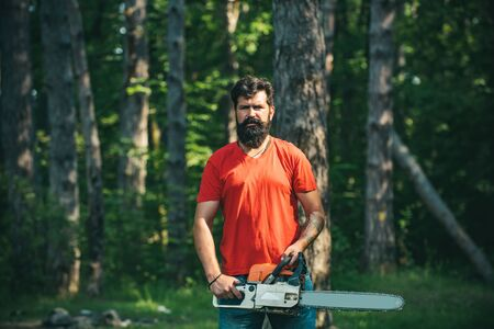 Lumberjack with chainsaw in his hands. Chainsaw. Deforestation is a major cause of land degradation and destabilization of natural ecosystems.