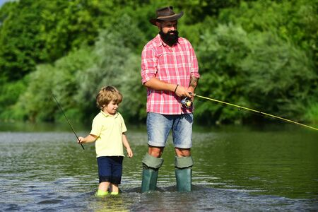 Father and son fishing and relaxing while enjoying hobby. Anglers. Fishermen father and son fishing in a river with a fishing rod.