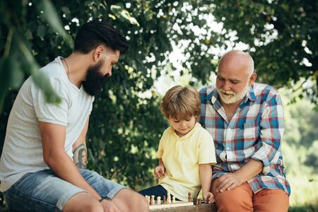 Cute little boy playing chess with Parents. Three different generations ages: grandfather father and son together. 스톡 콘텐츠