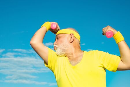 Like sports and muscles. Muscular senior sport man. Elderly man practicing sports on blue sky background.