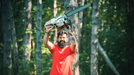 Lumberjack worker walking in the forest with chainsaw. A handsome young man with a beard carries a tree. Lumberjack on serious face carries chainsaw. Lumberjack concept.