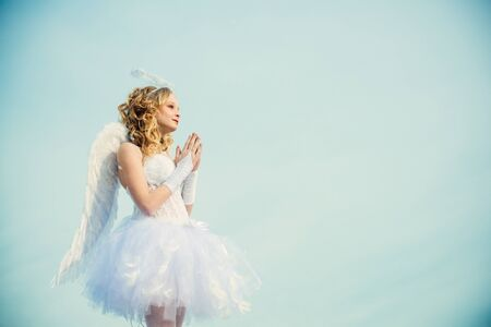 Cherub. Valentines day pray cupid. Heaven. Happy teenage angel girl pray. Festive Art Greeting Card. Girl angel with halo in white angel dress. Cute teen cupid on the cloud - heaven background. Фото со стока