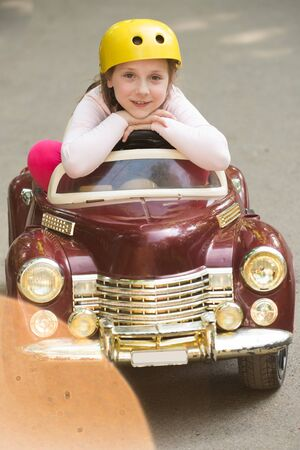 Sitting in small kids car. Happy childhood. Little girl walk in adventure park. Happy Lifestyle portrait of a beautiful young model girl with a sweet smile. Banco de Imagens