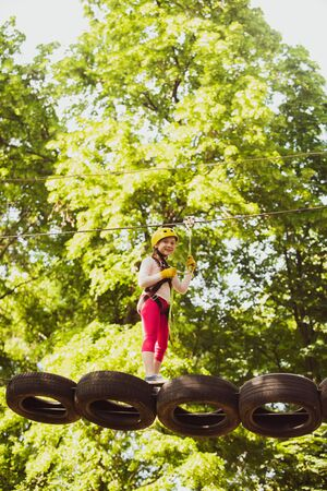 Little girl climbing on high rope park. Little girl climbing in adventure activity park with helmet and safety equipment. Children summer activities. Little girl playing on the playground. Stock Photo