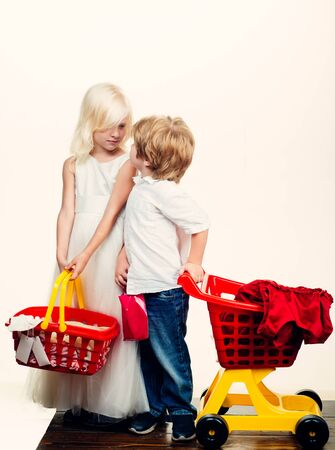 Girl and boy children shopping. Couple kids hold plastic shopping basket toy. Kids store. Mall shopping. Buy with discount. Buy products. Play shop game. Cute buyer customer client hold shopping cart Foto de archivo - 132078249