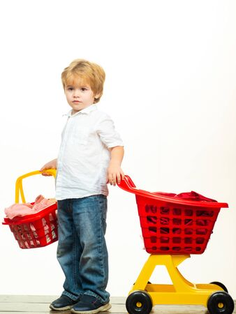 Cute buyer customer client hold shopping cart. Kids store. Boy child shopping. Big purchase. Kid hold plastic shopping basket toy. Buy with discount. Family shopping. Buy products. Play shop