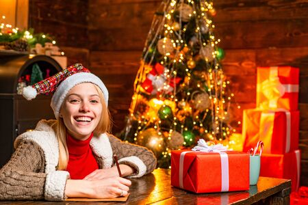 Beautiful woman in Santa hat helper with Christmas gift in a red box. Rituals for the New Year. Christmas and happiness concept. Reklamní fotografie