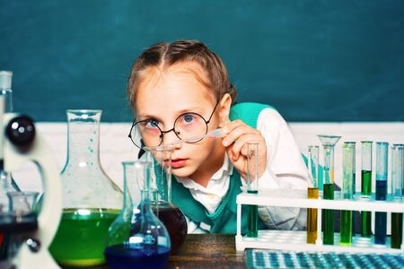 A chemistry demonstration. Back to school. Child from elementary school. Portrair close up. They carried out a new experiment in chemistry.