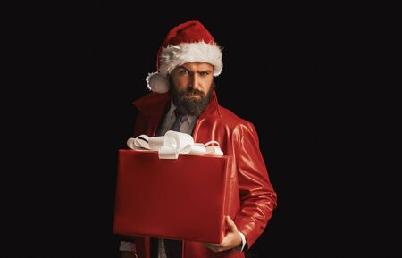 Bearded modern santa on black background wishes Merry christmas and Happy new year. Christmas gift. Stock Photo