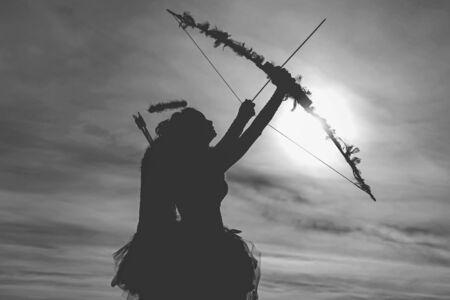 Archer de fille d'ange adolescent sur le coucher du soleil. Silhouette d'un cupidon. Vue latérale de l'archer adolescente contre le coucher du soleil. Le petit cupidon mignon tire un arc. Notion d'amour Banque d'images