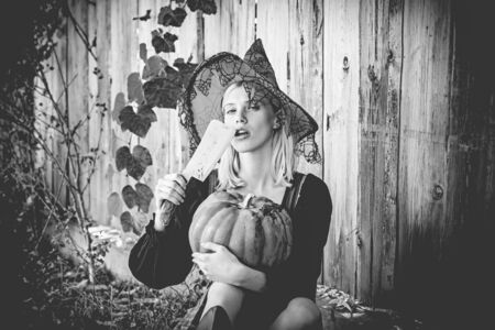 Halloween woman. Attractive witch holding pumpkin and knife for a trick or treat. Woman dressing in Halloween costume with orange witchs hat for a themed party. October festival. Wood background.