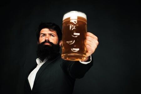 Handsome bearded man drinking beer. Portrait of handsome young man tasting a draft beer. Man holding mug of beer. Man holds glass of beer. Stok Fotoğraf