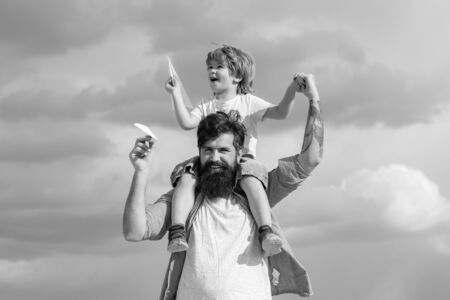 Child sits on the shoulders of his father. Family Time. Enjoy. Portrait of happy father giving son piggyback ride on his shoulders and looking up.