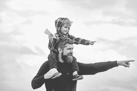 Happy fathers day. Dad and son are playing on sky background. Father and son building together a paper airplane. Portrait of happy father giving son piggyback ride on his shoulders and looking up