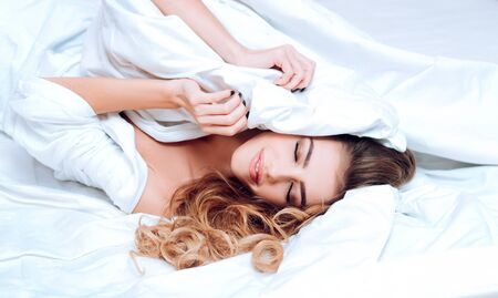 Good morning. Young woman holding in hands pillow in bed. Young woman sleeping in bed with pillows at home. Joyful woman wake up on a bed. Sleepy and lazy person slowly posing alone. Standard-Bild - 132316726