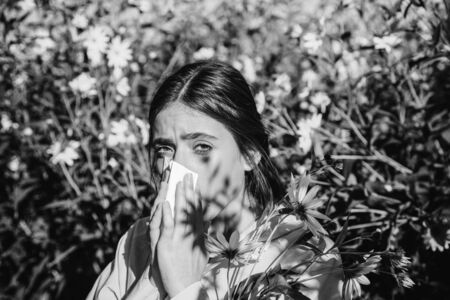 The girl suffers from pollen allergy during flowering and uses napkins. Beautiful sexy young woman lies on flowers background. Allergy. Stock fotó