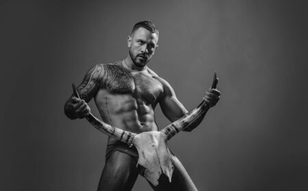 Dominantning in the foreplay sexual game. Dominate obey undress seduce a partner. Shop with Bondage and bdsm produce. Brutal handsome man with tattooed body. Men fashion Brutal models. 免版税图像