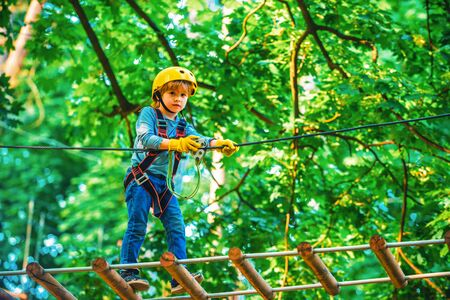 Kids boy adventure and travel. Adventure climbing high wire park. Early childhood development. Cute child in climbing safety equipment in a tree house or in a rope park climbs the rope 写真素材 - 132265661