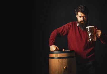 Emotional funny bearded drunk hipster holds craft bottled beer. Beer in the US. Lager and dark beer with keg or barrel of beer.